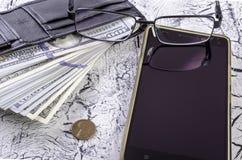 Pengar i plånbok, exponeringsglas och en smartphone Royaltyfri Bild