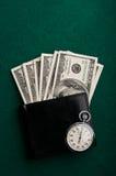 Pengar i plånbok och stopwatch Arkivfoto