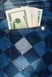 Pengar klibbar ut ur facket av hans jeans med bergkristaller Arkivbilder