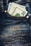 Pengar klibbar ut ur facket av hans jeans med bergkristaller Arkivbild