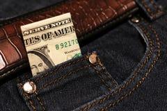 Pengar klibbar ut ur facket av hans jeans, som bakgrund Arkivbilder
