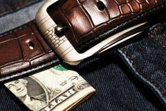 Pengar klibbar ut ur facket av hans jeans, som bakgrund Royaltyfri Bild