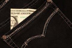 Pengar klibbar ut ur facket av hans jeans, som bakgrund Royaltyfri Foto