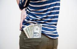 Pengar kommer ut från flickafacket Arkivfoton