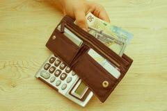 Pengar med den svarta plånboken på trätabellen handla pengar Royaltyfri Bild