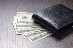 Pengar med läderplånboken på tabellen Arkivbilder