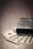 Pengar med läderplånboken på tabellen Arkivfoto