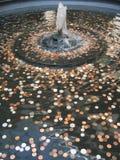 Pengar (mynt) i springbrunnen royaltyfria foton
