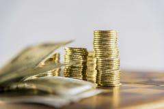 Pengar, mynt och anmärkningar på schackbrädet med vit bakgrund Royaltyfri Bild