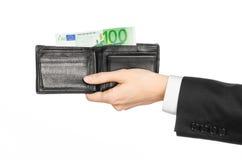 Pengar och affärsämne: räcka i en svart dräkt som rymmer en plånbok med 100 eurosedlar som isoleras på vit bakgrund i studio Arkivbilder