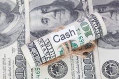 Pengar och affärsidé, dollarräkningarna som binds med ett rep, med ett tecken - kassa royaltyfri fotografi