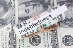 Pengar och affärsidé, dollarräkningarna som binds med ett rep, med ett tecken - skuld arkivfoto
