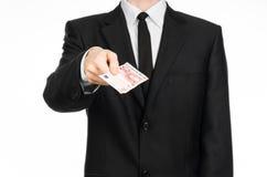 Pengar och affärstema: en man i en svart dräkt som rymmer en räkning av 10 euro och shower en handgest på en isolerad vit backgro Royaltyfri Foto