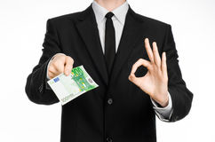 Pengar och affärstema: en man i en svart dräkt som rymmer en räkning av 100 euro och shower en handgest på en isolerad vit backgr Arkivbilder