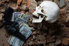 Pengar och en revolver nära skallen Brottsligt begrepp Royaltyfri Foto