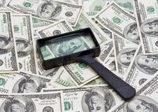 Pengar och förstoringsglas Arkivbild