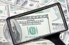 Pengar och förstoringsglas Arkivfoton