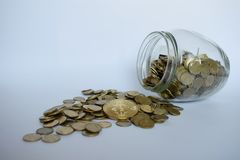 Pengar och flaska på ljus bakgrund En handinnehavkrus av pengar royaltyfri fotografi
