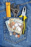 Pengar och hjälpmedel i jeansfack Arkivfoton