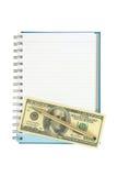 Pengar och penna över den tomma anteckningsboken Arkivbilder