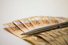 Pengar och penna Arkivfoto