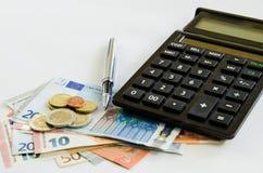 Pengar och räknemaskin arkivbild