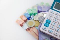 Pengar och räknemaskin för att budgetera Arkivfoto