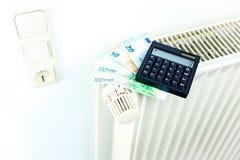 Pengar och räknemaskinen på ett element symboliserar den dyra värmen royaltyfri foto