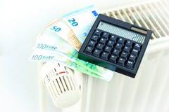 Pengar och räknemaskinen på ett element symboliserar den dyra värmen arkivbilder