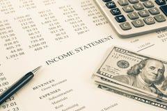 Pengar och rapporten för inkomstmeddelande i sepia tonar arkivfoton