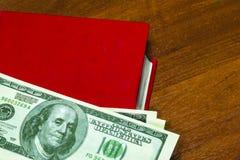 Pengar på boken 100 dollar royaltyfri foto