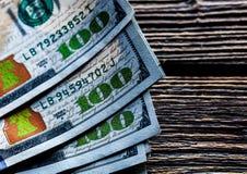 Pengar på en träbakgrund lott 100 dollar, affärssammansättning Arkivbild
