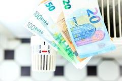 Pengar på ett element symboliserar de dyra uppvärmningkostnaderna royaltyfri foto