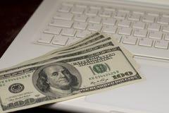 Pengar på ett tangentbord av en bärbar dator Arkivbilder