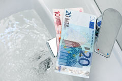 Pengar på klappet och det flödande vattnet Fotografering för Bildbyråer