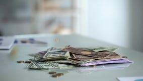 Pengar på tabellen, besparingar för utländsk valuta, bankinsättningen eller lönförtjänster, kassa arkivfoto