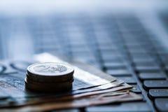 Pengar på tangentbordet av datoren Arkivfoton