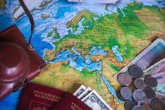 Pengar, pass och kamera på översikten Royaltyfri Bild