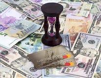 Pengar plast- kort för bank, timglas arkivbilder