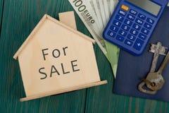 pengar, räknemaskin, litet hus med text & x22; För SALE& x22; på blått arkivbilder