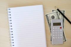 Pengar, räknemaskin, blyertspenna och mellanrumsanteckningsbok på wood bakgrund, Royaltyfria Bilder
