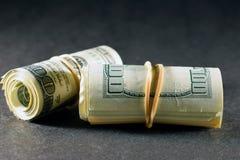 Pengar rullar på den mörka tabellen Arkivbilder
