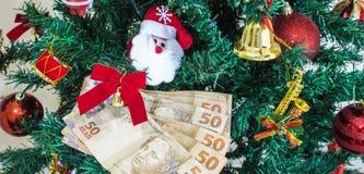 Pengar som är brasilian för julgåvor eller gåvapengar Julfilial och klockor arkivfoton