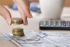 Pengar som är finansiella, affärstillväxtbegrepp, besparingar, slut upp av den kvinnliga handen som staplar guld- mynt Arkivfoto