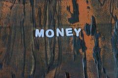 Pengar som är skriftliga i vit bokstäver Royaltyfria Bilder