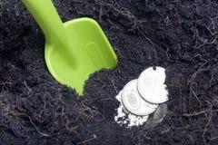 Pengar som begravas i jordningen Gropen grävas, mynt är i den En skyffel sticker fram från jordningen Royaltyfria Foton