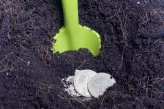 Pengar som begravas i jordningen Gropen grävas, mynt är i den En skyffel sticker fram från jordningen Arkivbild