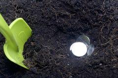 Pengar som begravas i jordningen Gropen grävas, mynt är i den En skyffel sticker fram från jordningen Fotografering för Bildbyråer