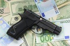 Pengar som en bakgrund och ett vapen Fotografering för Bildbyråer