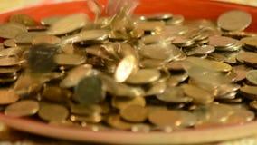 Pengar som faller in i koppen stock video